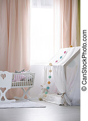 Crib and playhouse with canopy in modern nursery with big...