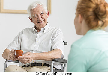 Coffee with carer - Elderly man on a wheelchair drinking...