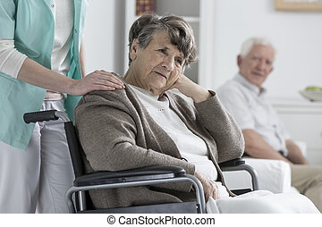 Worried older woman on a wheelchair in a nursing home