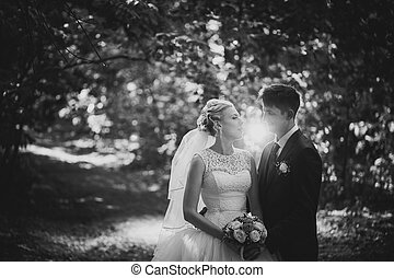 black and white photo portrait of the bride  groom on the forest