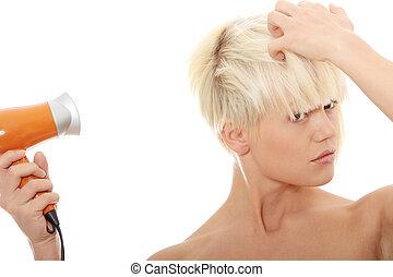 Blonde woman using hair drier