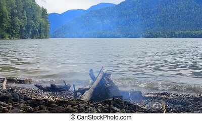 camp fire on shore of mountain lake. Rest near water and...