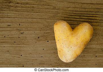 Heart shaped potato on old spruce wood board - Heart shaped...
