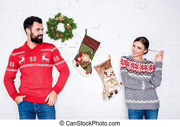 Flirting couple leaning on white wall with Christmas...