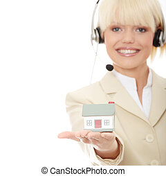Real estate - Young businesswoman in headset holding two...