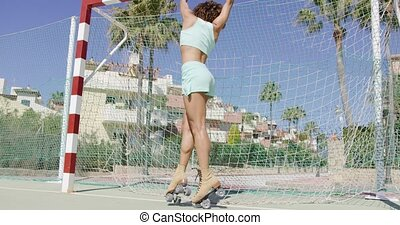 Fit girl in roller skates on playground - Back view of young...