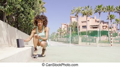 Woman in roller skates setting on music - Young smiling...