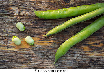 Fava beans - Fresh raw fava beans on a rustic wooden...