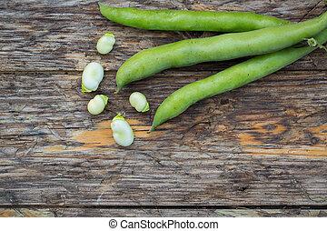 Fava beans - Fresh raw fava beans on a rustic wooden...