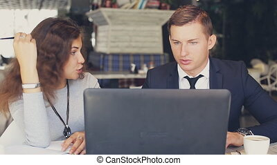 two workers with modern laptop in cafe - Man and woman with...