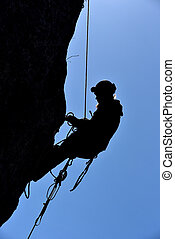 Silhouette of a rock climber hanging on the wall