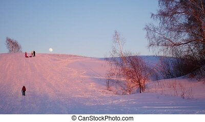 winter landscape. sunset time. people climb the snowy hill