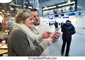 Senior couple with smartphone in hallway of subway -...