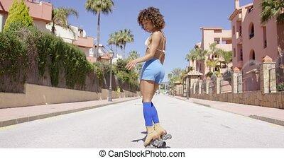 Female posing riding on roller skates - Female wearing blue...