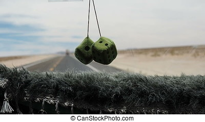 Hanging dices inside a moving car - Two green hanging dices...