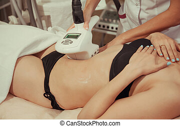 Beautiful woman getting cavitation treatment at beauty salon