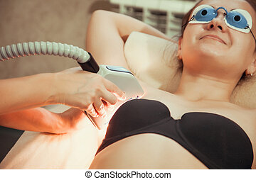 Young woman Receiving Laser Epilation Treatment On Underarms...