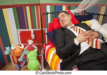 Mature man sleeping in playpan - Mature man wearing full...