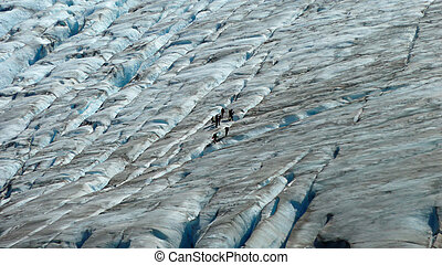Small group of people walking on Exit glacier in Alaska