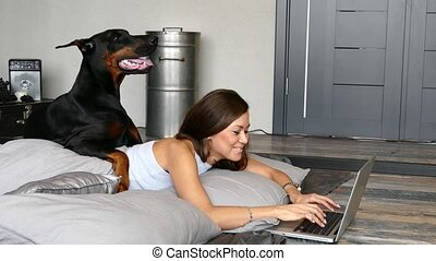 Young pretty woman with black doberman dog