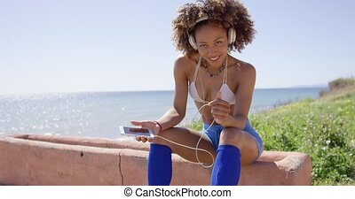 Female sitting listening music - Smiling female wearing...
