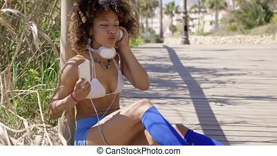 Fit girl listening to music - Young fit female in swimsuit...