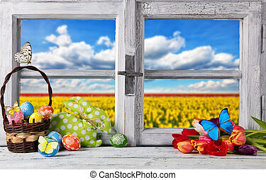 Easter colored decoration on wooden window, blur sky with...