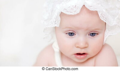baby crawling on bed in a white bonnet