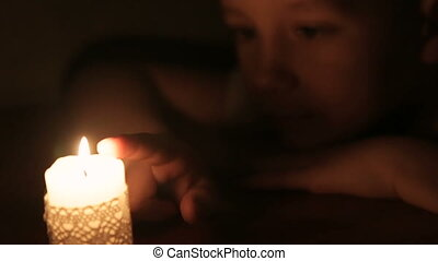 The boy touches the wax of a burning candle and smiles