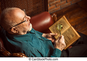 Literary critic - An old intelligent man reading a book in...