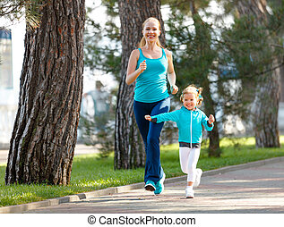 sport family. Mother and baby daughter jogging run on nature...