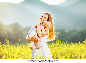 Happy family mother and baby hugging  nature in summer