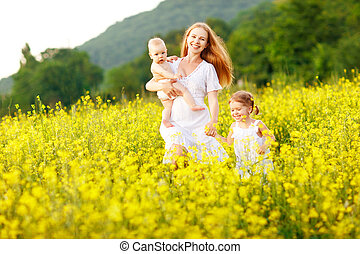 Happy family of mother and children run in the meadow of yellow flowers