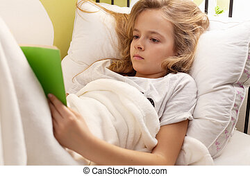 Young girl reading a book in bed, shallow depth