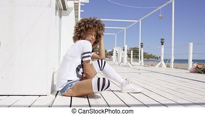 Female wearing sportive outfit sitting on floor - Smiling...