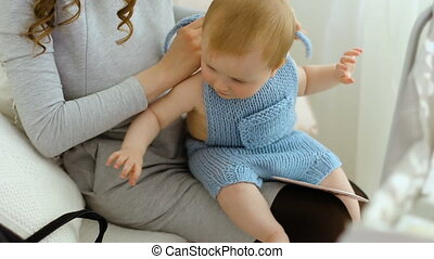 mother puts the child sitting on the couch in a knitted...