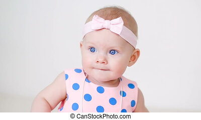 little girl in a pink polka dot dress with bandage on head