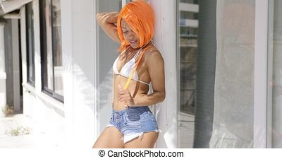 Female with orange hair posing - Female with bright orange...