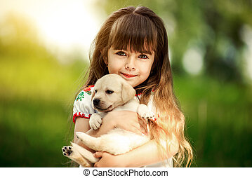 Little girl with a Golden retriever puppy. A puppy in the...