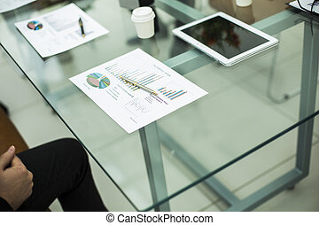 financial chart,glasses and pen on the workplace of the businessman
