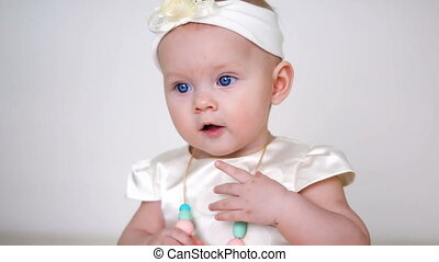 baby girl in white dress and headband sitting on the wooden...