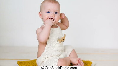little girl in knitted overalls sitting in the studio on a...