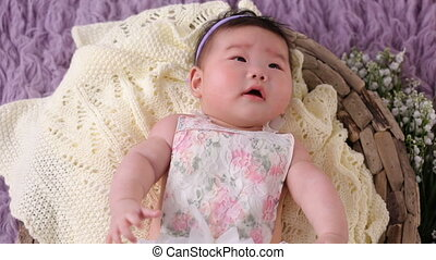 little asian baby girl lies in basket crib in dress and...