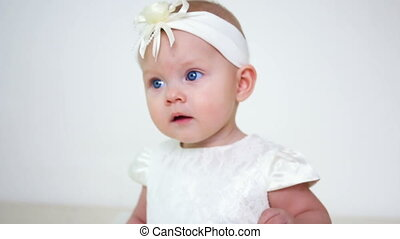 baby girl in white dress and headband sitting on a little...