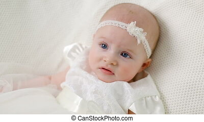 baby girl in white dress and headband and smiling in studio