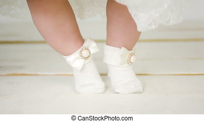 child's feet in a beautiful white socks on a wooden floor