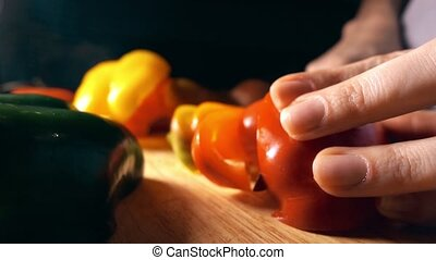 Amateur cook cutting juicy red sweet pepper. Healthy eating...