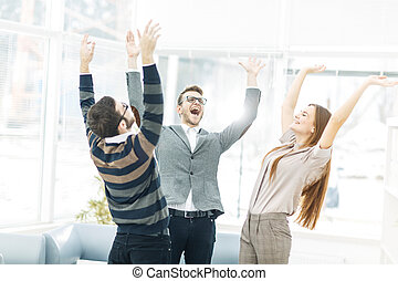concept of victory - the jubilant business team standing in...
