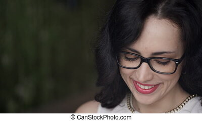 Closeup shooting of woman face smiling reading messages outdoors