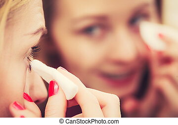 Woman using cotton pad to remove make up - Skin complexion...